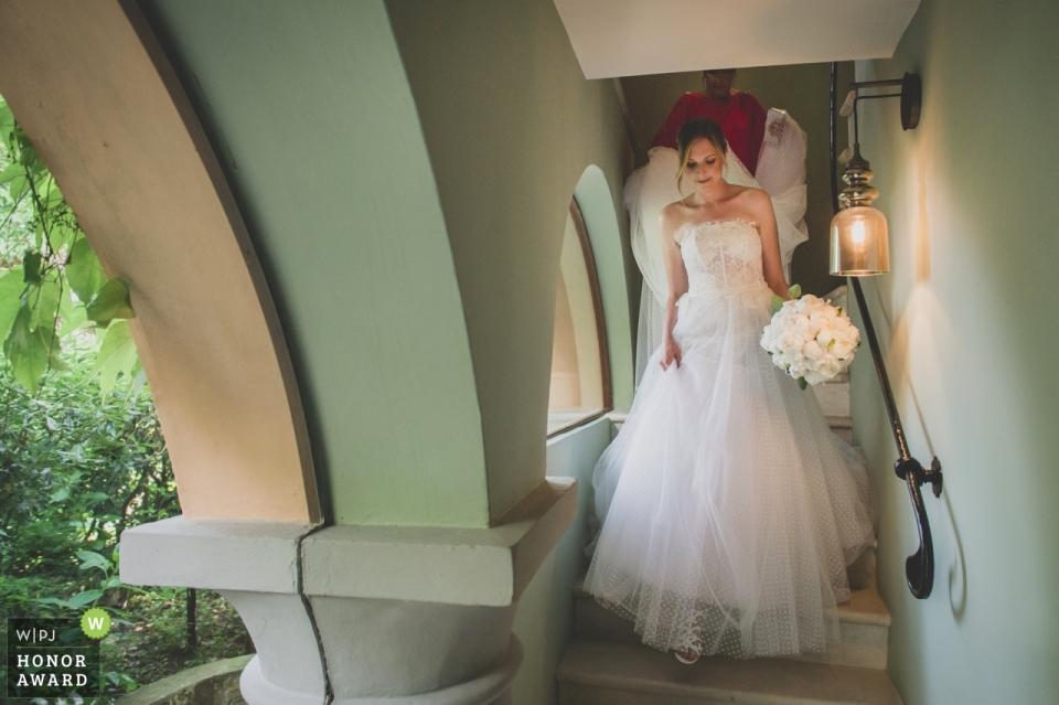 Image de photojournalisme de mariage de la mariée descendant les escaliers à Albereta Relais & Châteaux