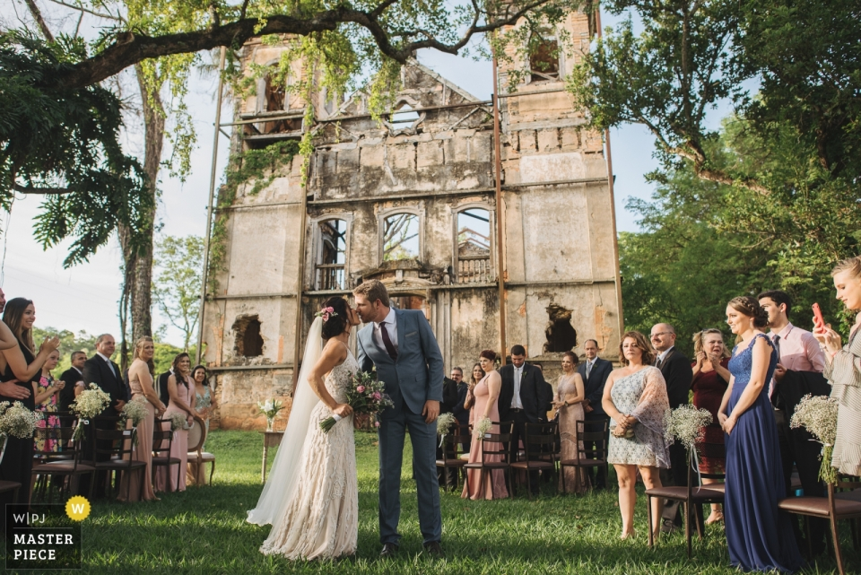 Fazenda Jagoara Velha - Minas Gerais  wedding shot of a couple kissing during outdoor ceremony under drees on the grass