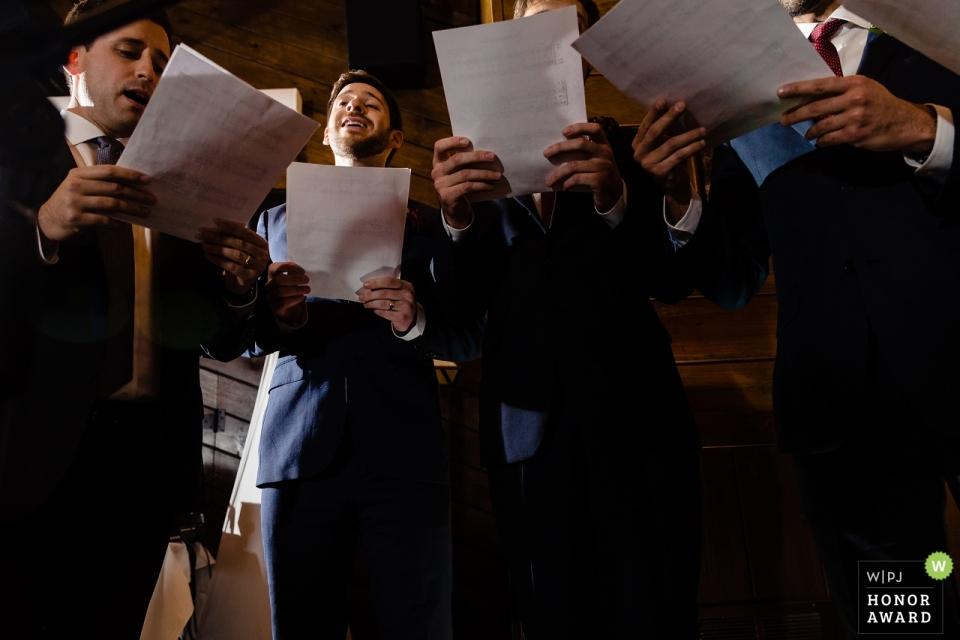 Photographie de mariage documentaire à Migis Lodge, Maine - Un groupe a capella sérénade le couple lors de la cérémonie
