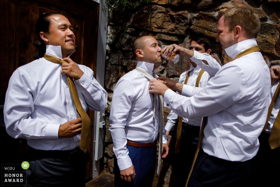 Hochzeitsfotojournalismusbild des Bräutigams und der Trauzeugen, die ihre Bindungen an der Rotwild Creek Valley Ranch tun
