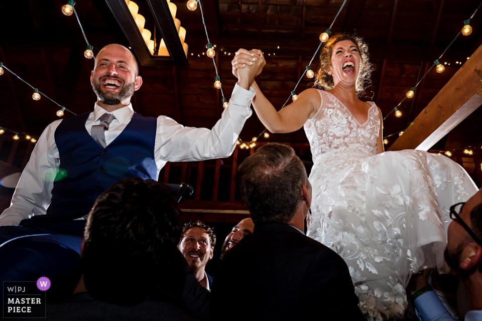 La mariée et le marié sont levés pour la danse Horah lors de leur réception   Linekin Bay Resort Boothbay Harbor dans le Maine