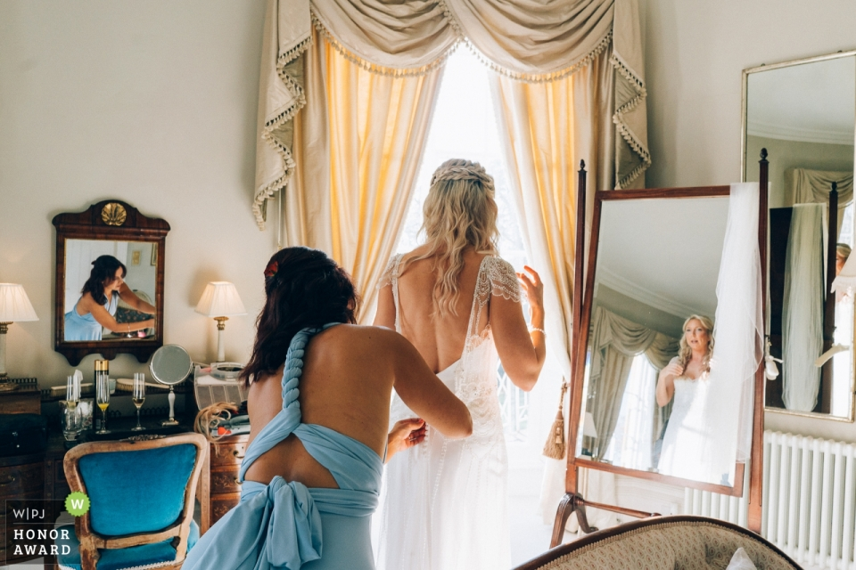Wedding getting ready photo shoot in North Cadbury Court, Somerset UK - Bridesmaid helping bride into wedding dress with reflections in mirrors