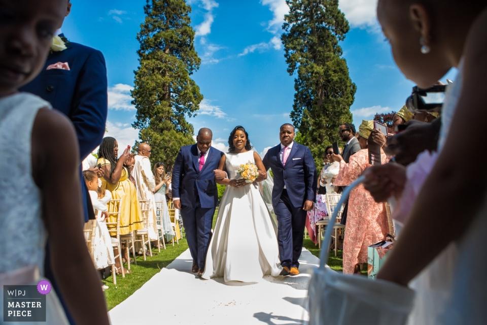 La mariée est escortée dans l'allée pour son mariage en plein air à la Kingston Bagpuize House, à Londres