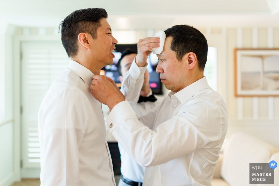 Wequassett Resort Wedding Photographer |  The Groom is helping his groomsmen to get ready with is tie and getting the sweat wiped from his brow by another