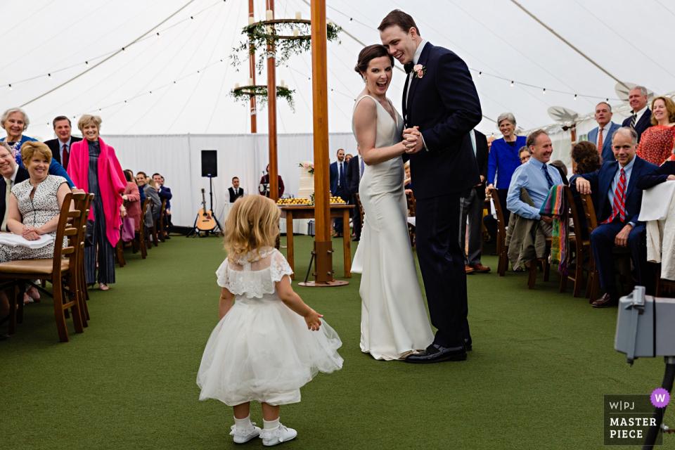 Hardy Farm à Fryeburg dans le Maine Photographie de mariage   Les mariés craquent à la fille de fleur qui a été attachée aux côtés de la mariée toute la journée