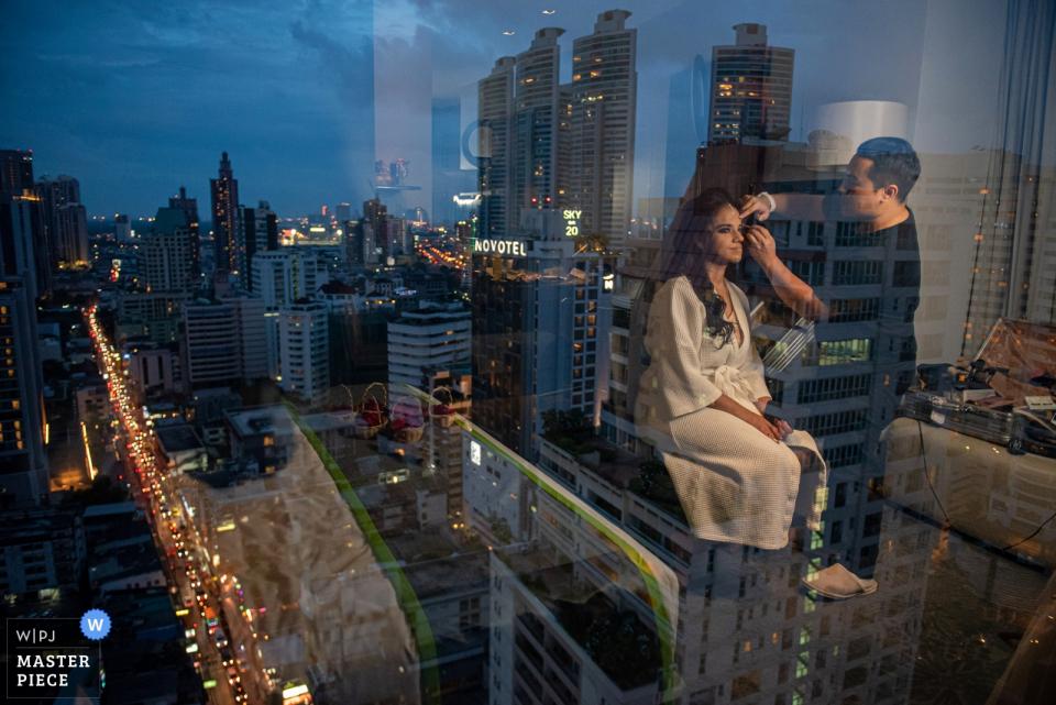 """Holiday Inn Sukhumvit Hochzeitsfotograf: """"Das Spiegelbild ist das, was ich über die Zeit und Atmosphäre des Make-ups der Braut erzählen möchte, bevor die Party beginnt zu feiern."""""""