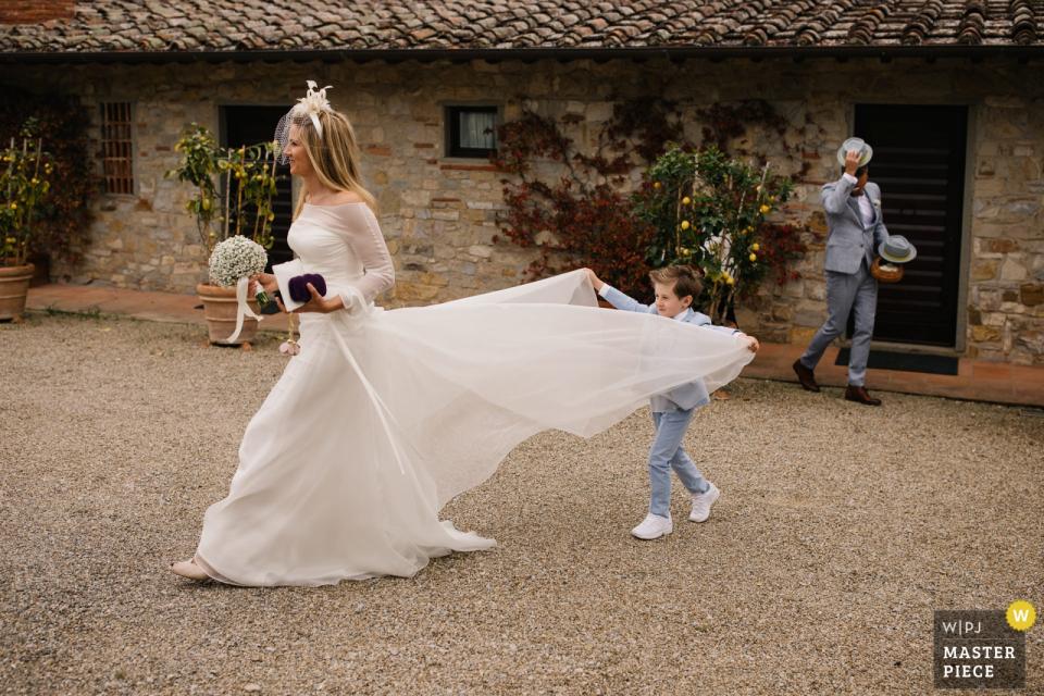 Castello di Spaltenna, Toskania   Ślubna fotografia pokazuje młodego syna pomaga jego matki z jej suknią