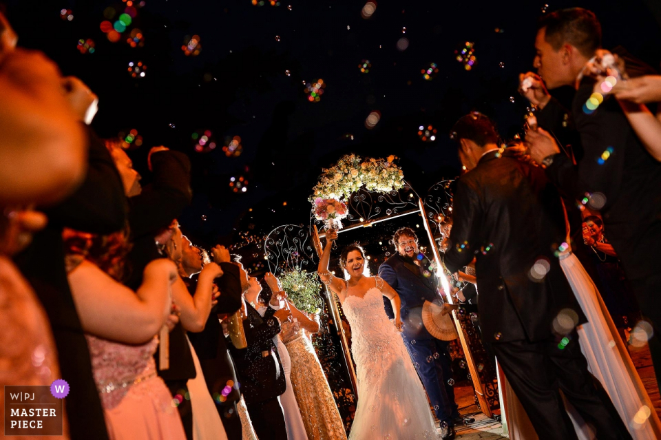 Paioça do cabloco couple leaving the ceremony at night in this wedding photograph.