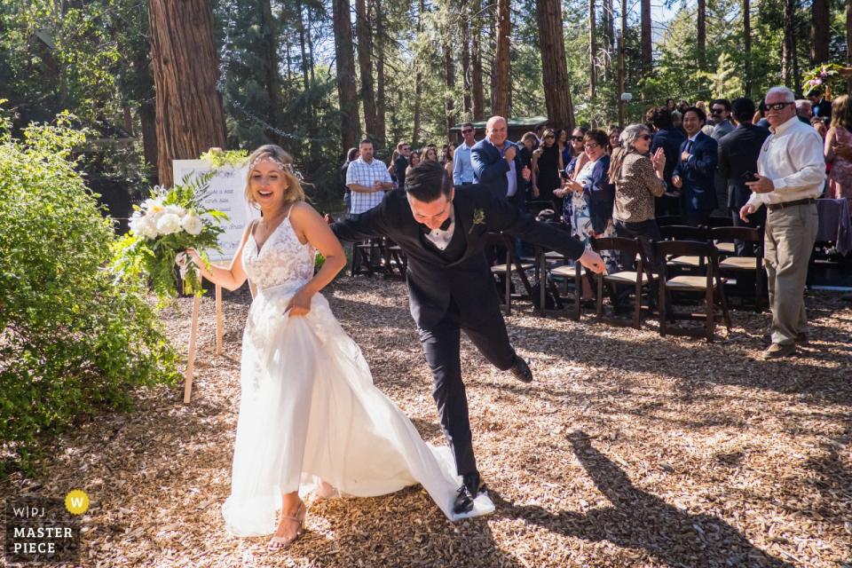 加利福尼亚州Idyllwild草莓溪彩虹酒店婚礼摄影师 - 新郎在退出仪式时不小心踩到了新娘的衣服。