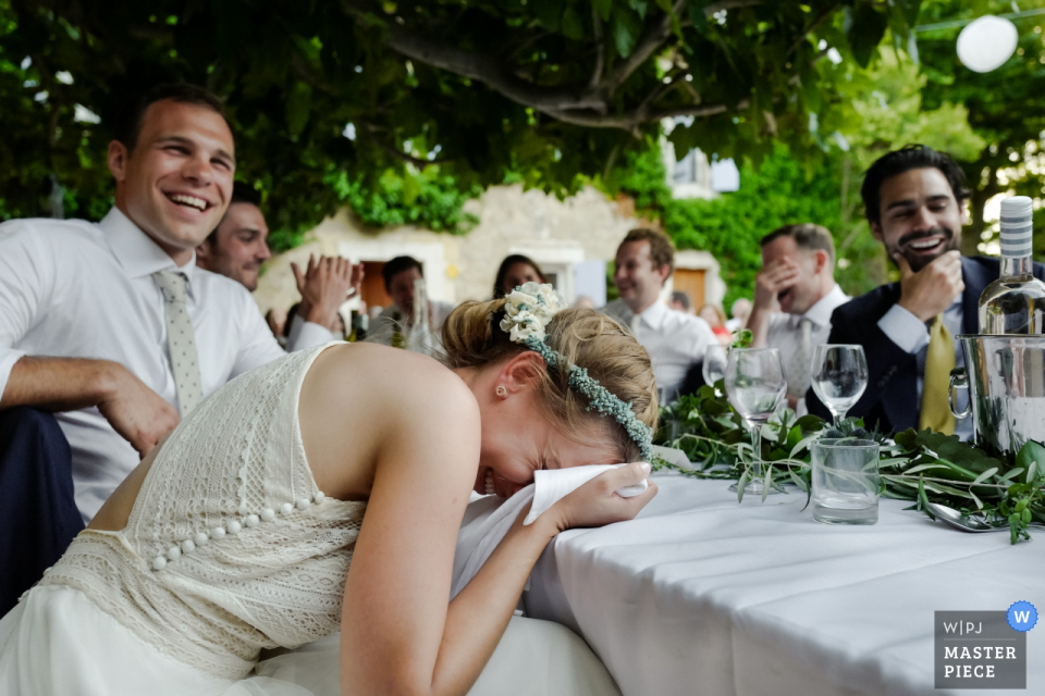 The guests and bride cannot stop laughing during a funny speech at her Chateau du Puits es Pratx, Ginestas wedding in this award-winning photo by a Montpellier, France wedding photographer.