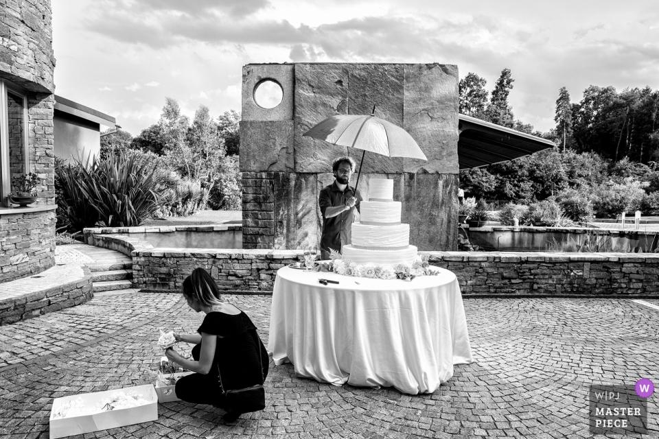 De bruidstaart staat klaar en wacht in Le Pinete, Viggiù op deze zwart-witfoto van een bekroonde bruiloftsfotograaf in Milaan, Lombardije.