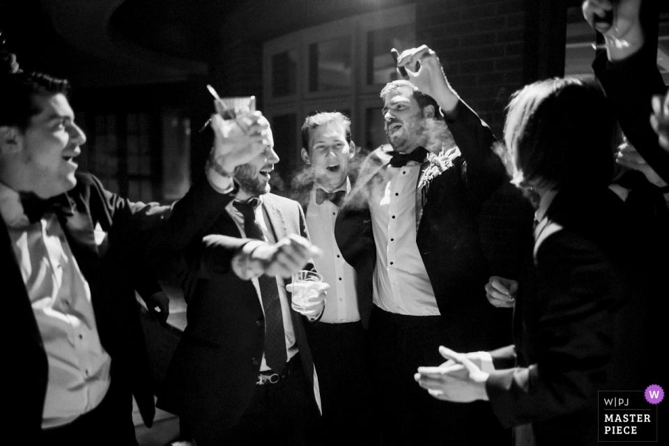 Vermont-Gasthaushochzeitsfoto, das den Bräutigam und Groomsmen genießen Zigarren zeigt