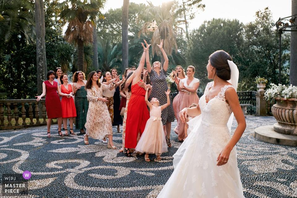 Panna młoda rzuca swój bukiet przed Villa Durazzo na zdjęciu ślubnym skomponowanym przez Savonę, fotografkę z Ligurii.