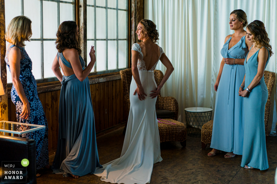 Sodo Park Seattle WA wedding venue photos | Maid of honor giving the looking good sign to bride after getting dressed.