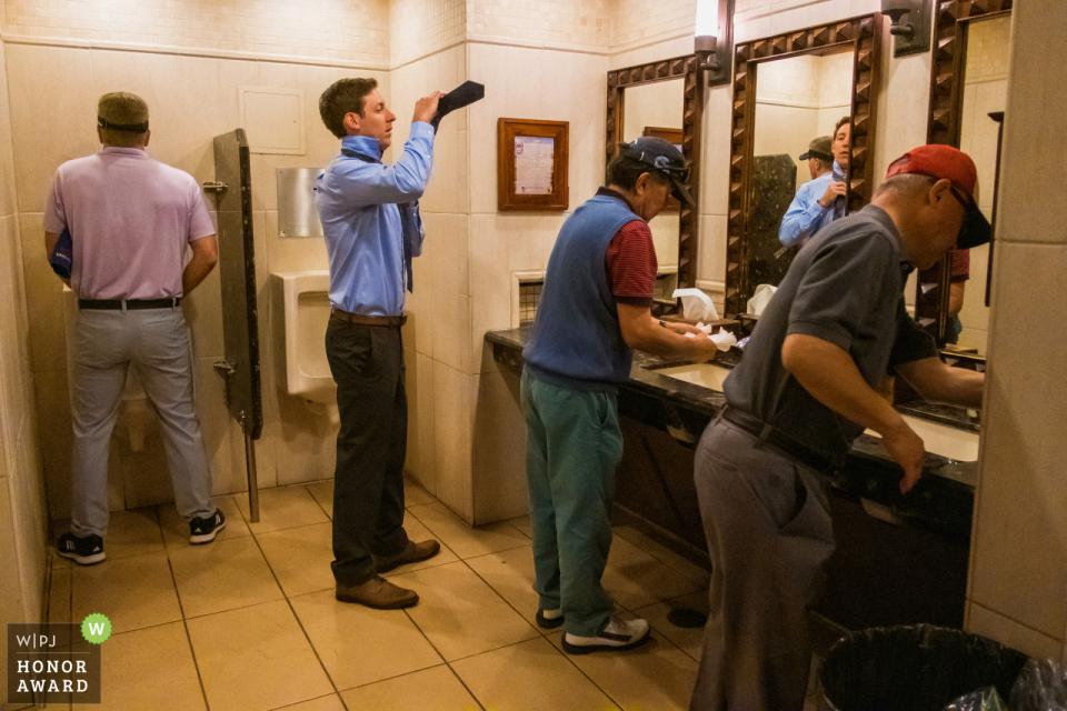 加利福尼亚,阿罗约特拉布科,Mission Viejo高尔夫俱乐部婚礼场地照片| 伴郎在阿罗约·特拉布科高尔夫俱乐部的男洗手间系领带