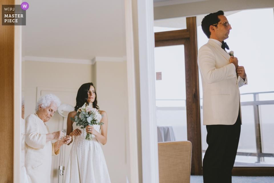 Mersin, Hilton Hotel / Turkije Trouwfoto's van de grootmoeder van de bruid die haar op de spiegel voorbereidt en de bruidegom de laatste controles uitvoert in de volgende kamer