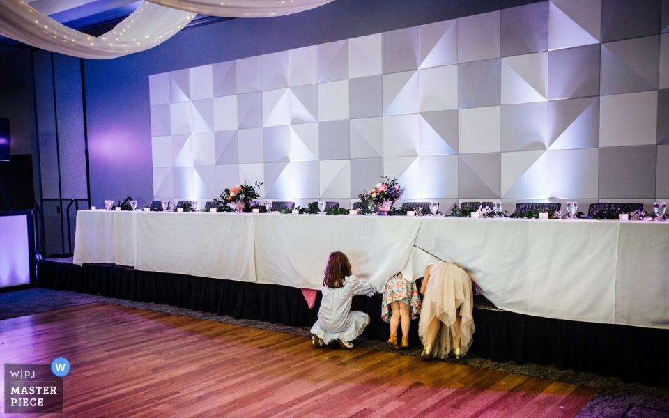 Photo montrant des fillettes essayant de se cacher sous la table d'honneur au centre de conférences Scott