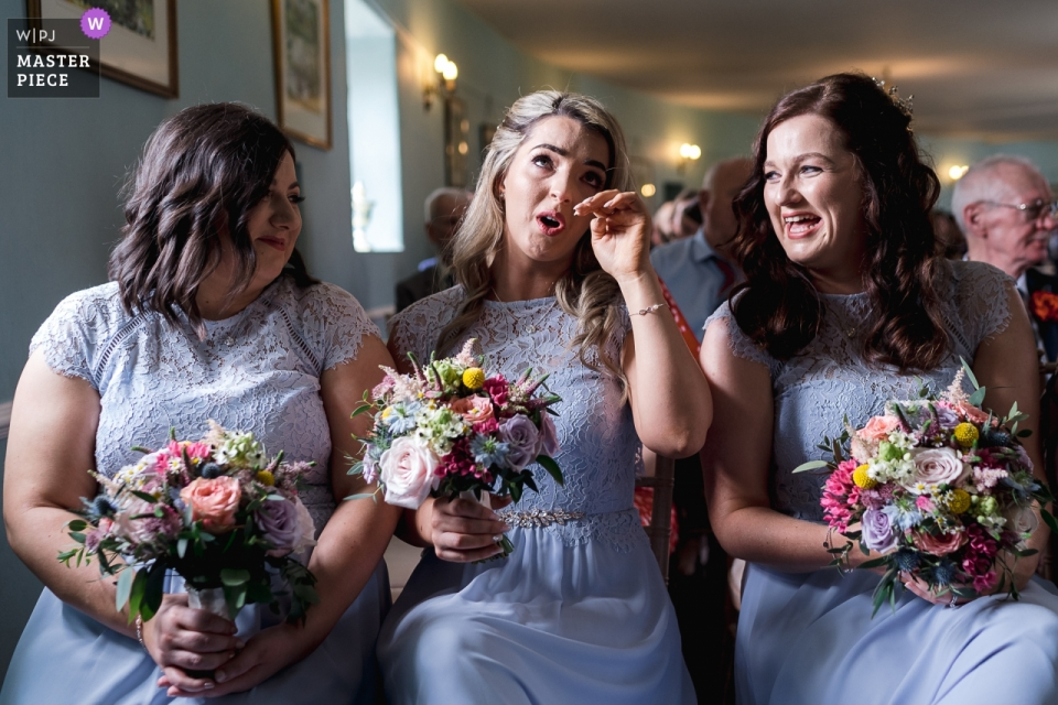 A bridesmaid tears up during wedding ceremony at the Lissanoure Castle, Glens of Antrim.