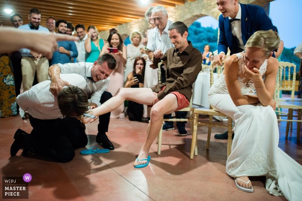 Hochzeitsempfangsphotographie eines Bräutigams mit verbundenen Augen, der nach dem Strumpfband am falschen Ort an einer Le Cantorie-Hochzeit in Gussago sucht.