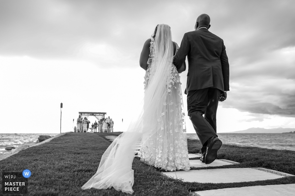 Black and white photograph of a bride with her father walking down the aisle to a Villa Premiere wedding. Vallarta, Mexico photographers.