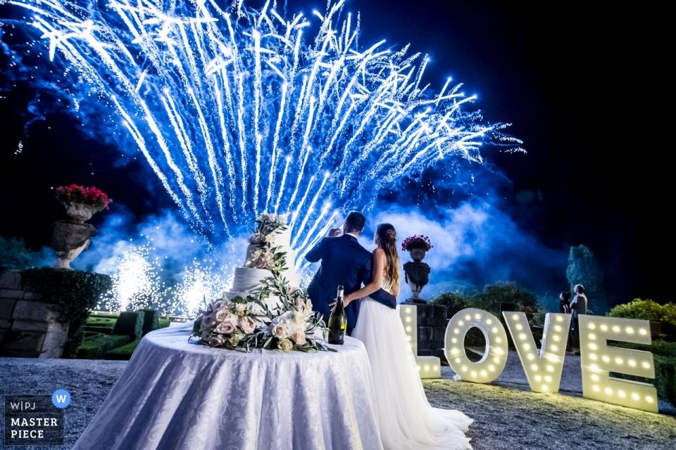 Fotografía de la recepción de boda de Villa Orsini Colonna de la novia y el novio mirando fuegos artificiales azules con el pastel de bodas en primer plano.