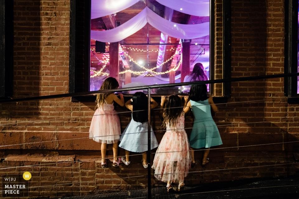 Dumbo Loft wedding photo of little girls peeking the recetpion hall.
