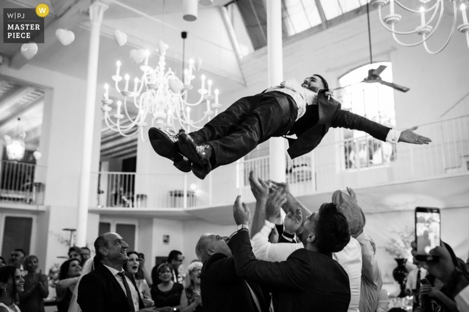 Trouwlocatie Locatie: La Madonnina Cantello - Foto van de bruidegom wordt door zijn vrienden in de lucht gegooid.