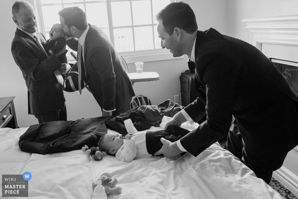 Westlake Village Inn,Westlake Village,California的纪录片婚纱摄影新郎与他的父亲和他的姐夫一起打扮双胞胎婴儿。