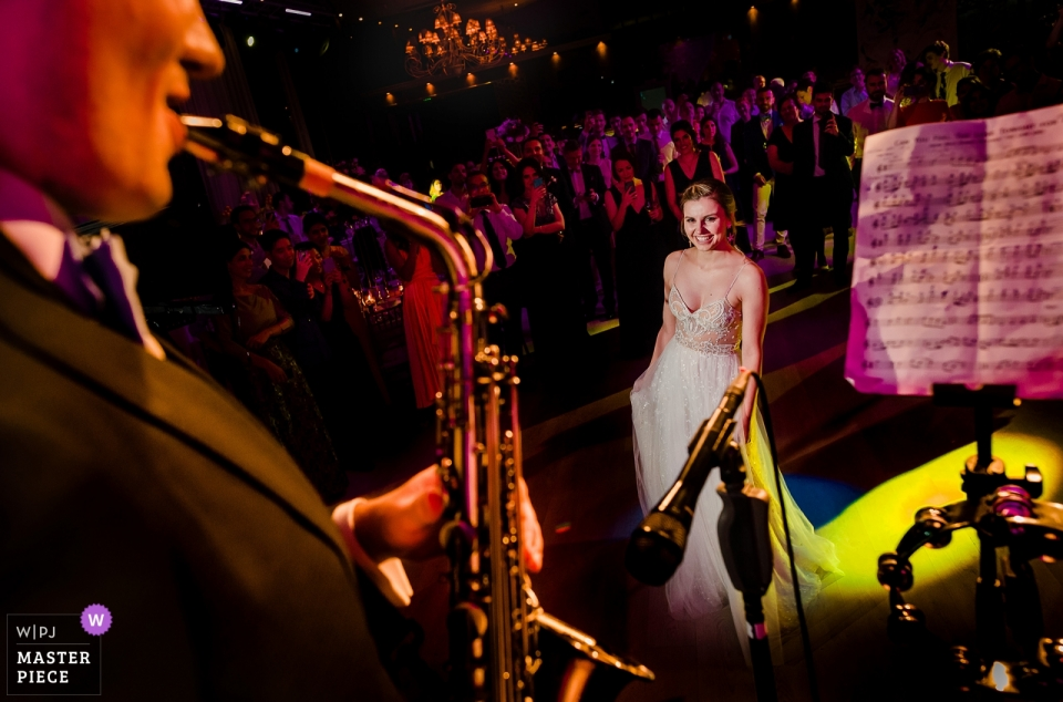 Bamboo Club, Bucharest Wedding venue photography | Bride watches as groom plays Lion King theme on the saxophone