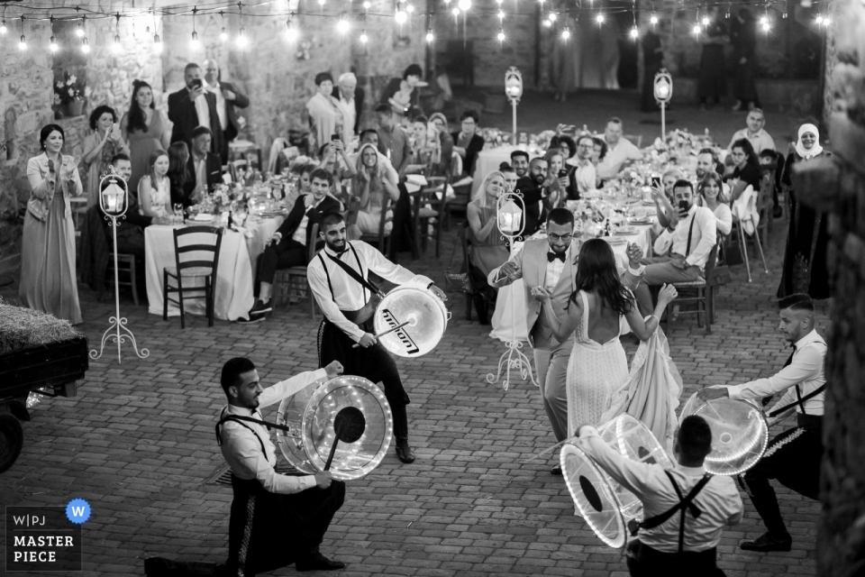 Trouwfotografie uit Podere Conti Toscane - Foto van bruid en bruidegom dansen met Arabische muzikanten spelen