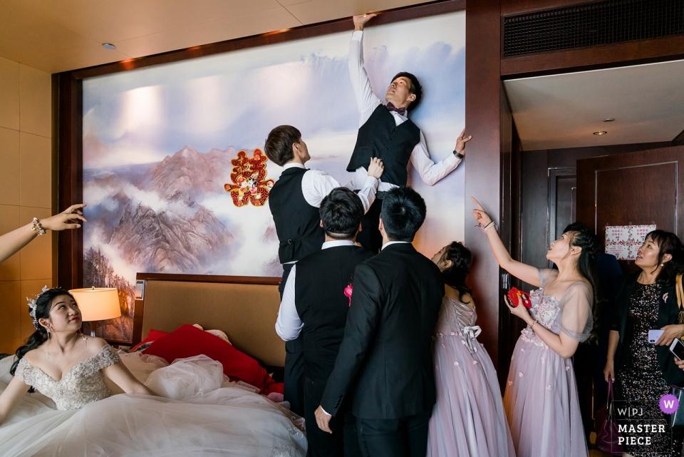 Hochzeitstag-Fotografie am Peking-Shangri-La China-Weltgipfel-Flügel - Foto des Bräutigams, der nach den Schuhen der Braut sucht