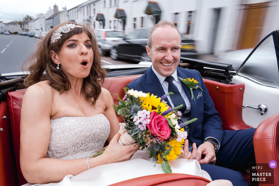 Orange Tree House, Greyabbey, Northern Ireland documentary wedding photographer | Mustang Driver puts foot down in wedding car with bride and groom in the backseat - Slow shutter bridal ride