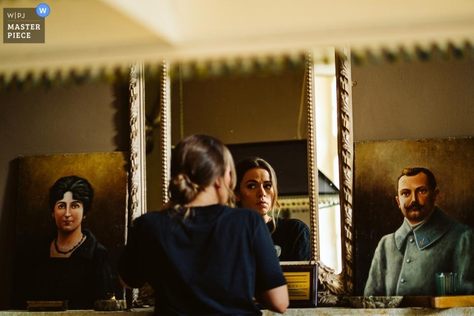Hochzeitsfotografie im Chateau Lartigolle, Frankreich - Vorbereitung der Brautjungfer während der Vorbereitungssitzung mit Gemälden und einem Spiegel