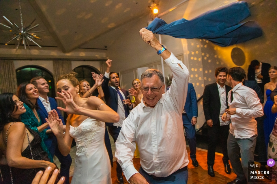 Hotel Bel-Air, Los Angeles, California Wedding Photographer | The bride dodges her step-father's jacket being swung in the air on the dance floor.