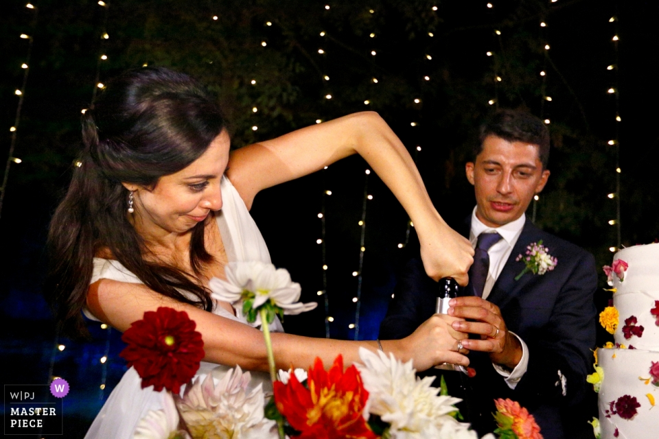 Huwelijksfotografie bij Convento dell'Annunciata, Medole, Mantova Receptie / Cake. Problemen met het openen van een fles champagne ... de bruid komt tussenbeide.