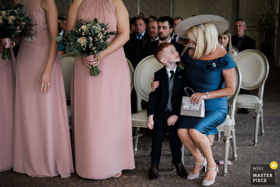 Wedding Reportage Photography from Venue: Corick House Hotel, Northern Ireland | The page boy receives a hug from his grandmother after successfully delivering his parent's rings to the officiant