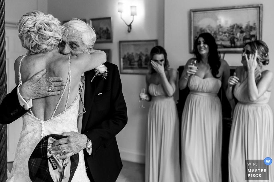 Photographie de reportage sur le mariage à Iscoyd Park - Un père embrassant une demoiselle d'honneur dans le dos en pleurant