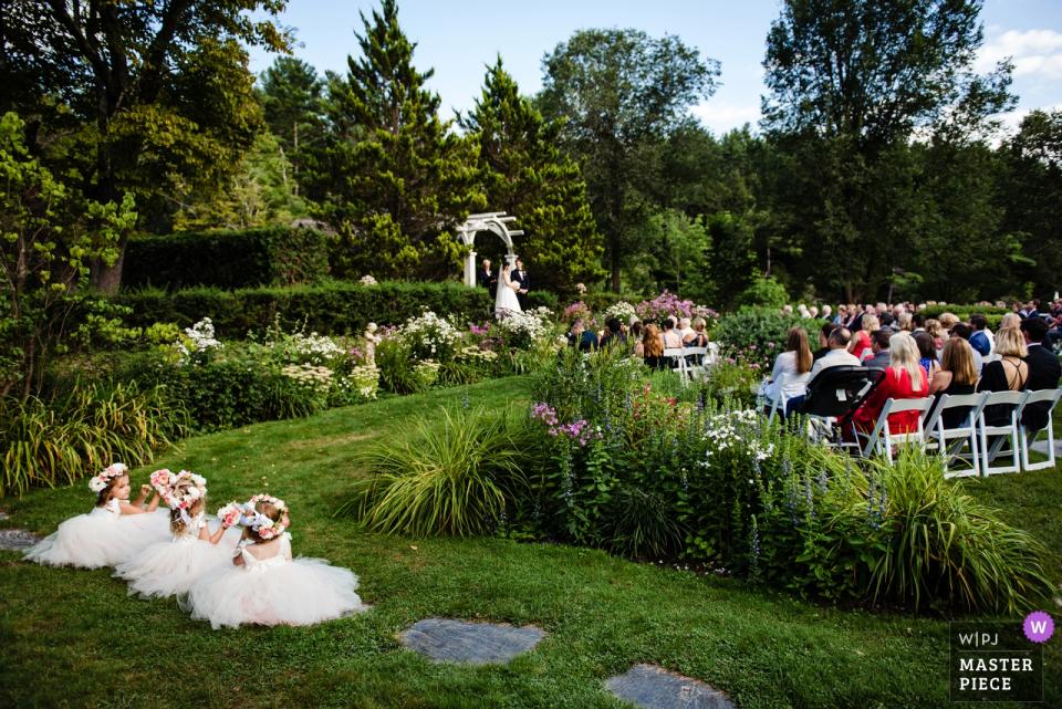 Photographie de la cérémonie de mariage à Hamilton House - South Berwick, Maine - Des fillettes en fleurs regardent la cérémonie de leur siège préféré.