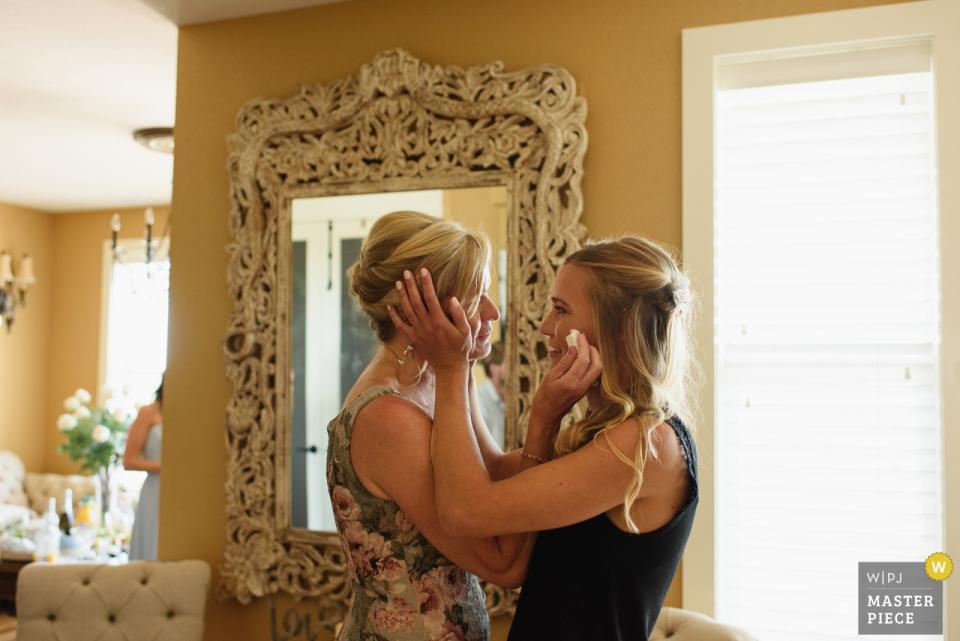 Sound-to-Sea-Beach-Club, Corolla, NC Hochzeitsfotografie - Braut und Mutter umarmen sich, während sie sich vor der Zeremonie fertig machen
