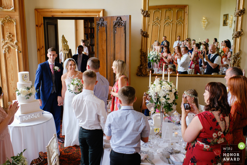 Stoke Rochford Hall, Grantham, UK wedding venue photographer said this: As the bride & groom entered the dining room, I shot with the camera above my head to include the guests in the mirror.