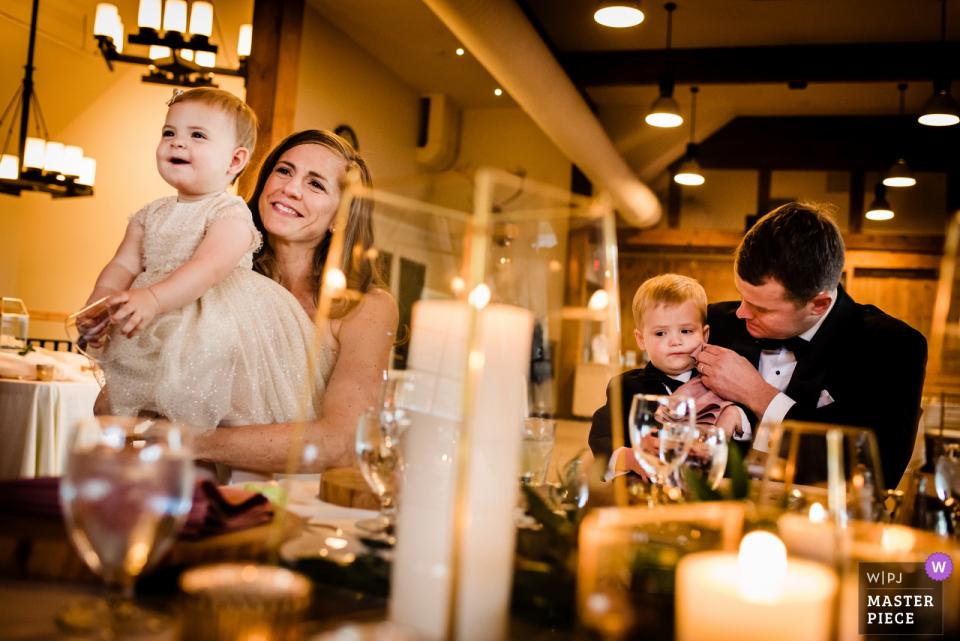 Sugarbush Resort - Hochzeitsfotografie in Warren, VT | Braut und Bräutigam hören sich Toasts an und essen mit ihren beiden Kindern zu Abend