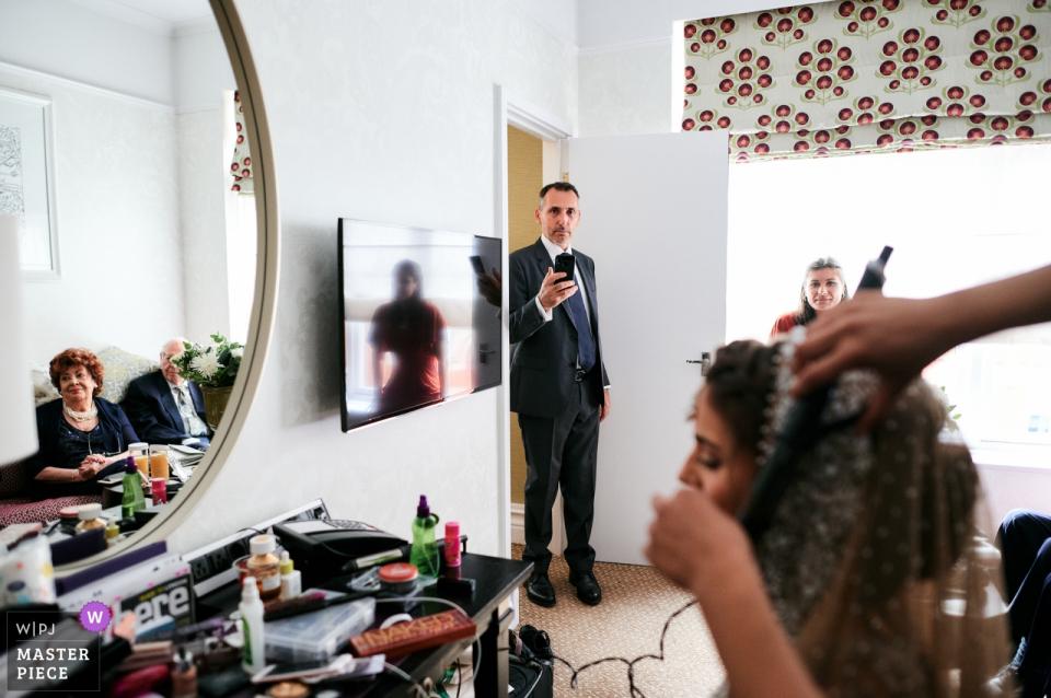 St Ermins Hotel, London, UK Hochzeitsfotografie   Vater und Großeltern der Braut sehen zu, wie sie sich fertig macht.