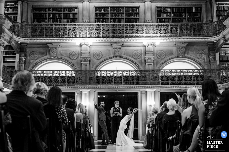 Peabody Library - Baltimore MD wedding ceremony pictures of the bride and groom celebrating with arms up in the air.