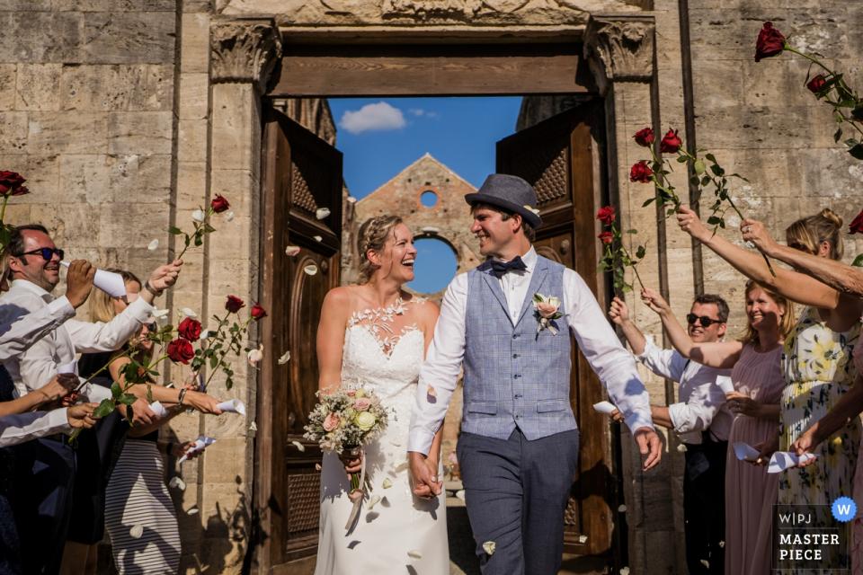 Fotografia ślubna z opactwa San galgano, Agriturismo San Galgano, Siena   Konfetti po ceremonii z mostem róż