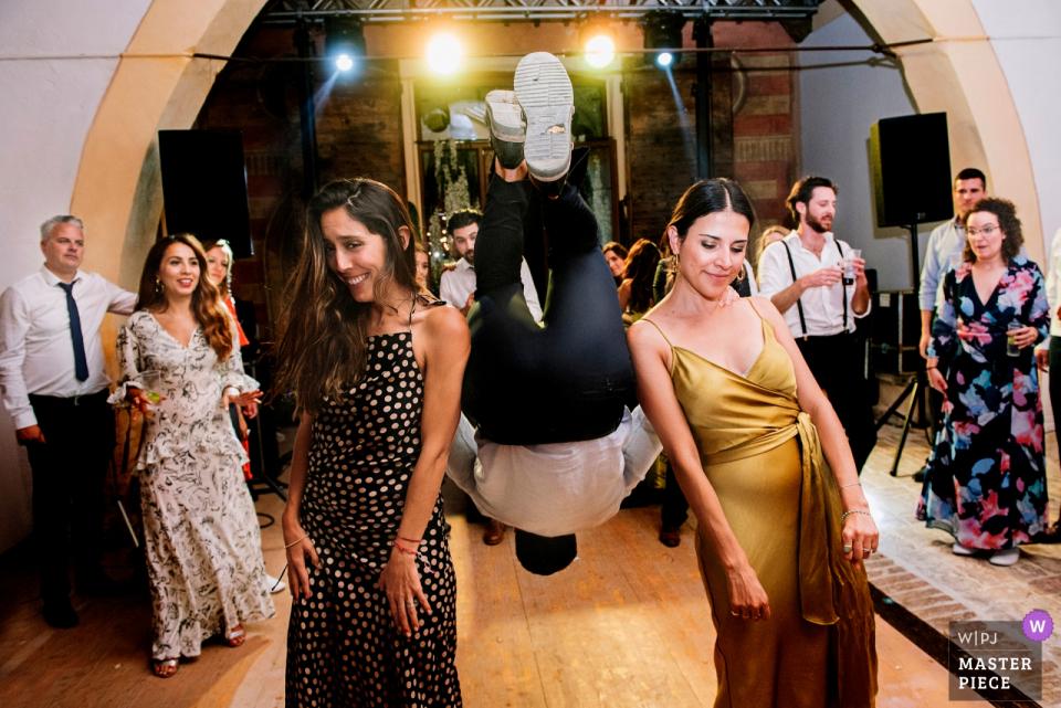 Invitados de Villa di Montefreddo involucrados en bailes locos con la música de 60 en el fondo - Imagen de baile de la recepción nupcial