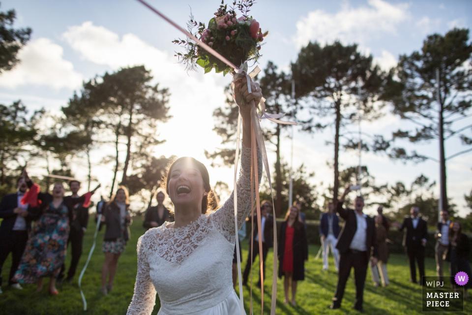 Reception Venue : Tir au Vol Arcachon image contains: Bride throws the bouquet with Ribbons