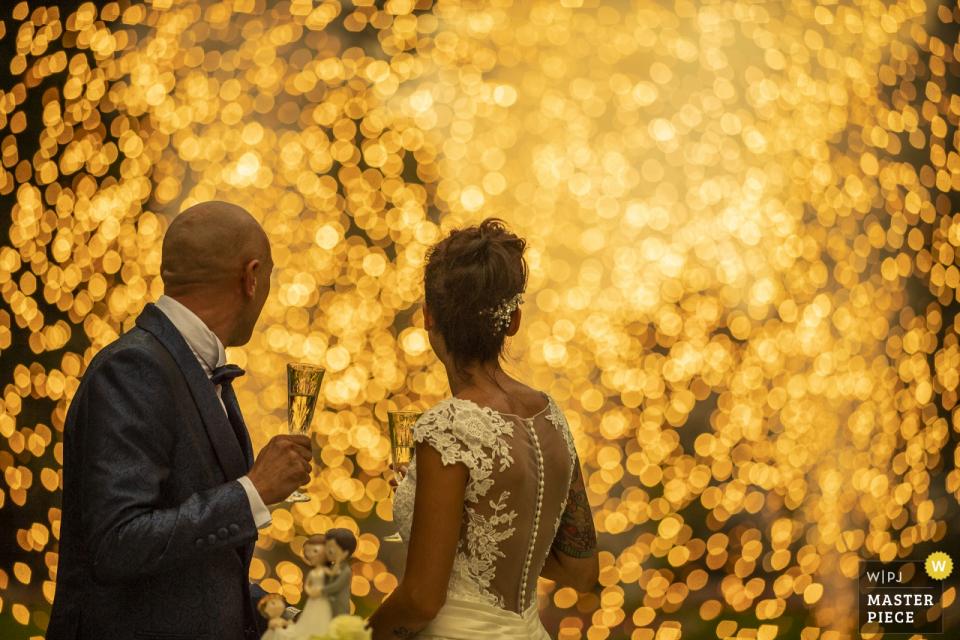 Die Braut und der Bräutigam, eingewickelt in die warmen Lichter des Feuerwerks an ihrem Empfang, Villa Acquaroli Carvico