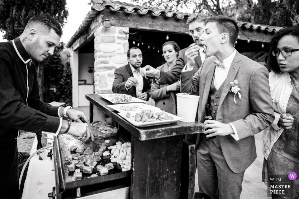 Domaine des Rives wedding reception image of the groom enjoying some snacks from the grill.