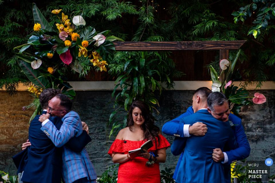 美国加利福尼亚州圣莫尼卡圣迈克尔斯餐厅的婚礼照片-两名新郎拥抱亲人