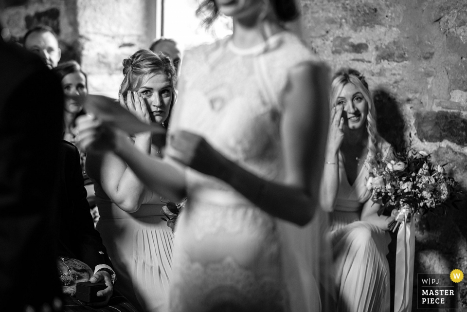 Healey Barn, Northumberland wedding reportage | Photo of Two bridesmaids wipe away their tears midway through the wedding ceremony